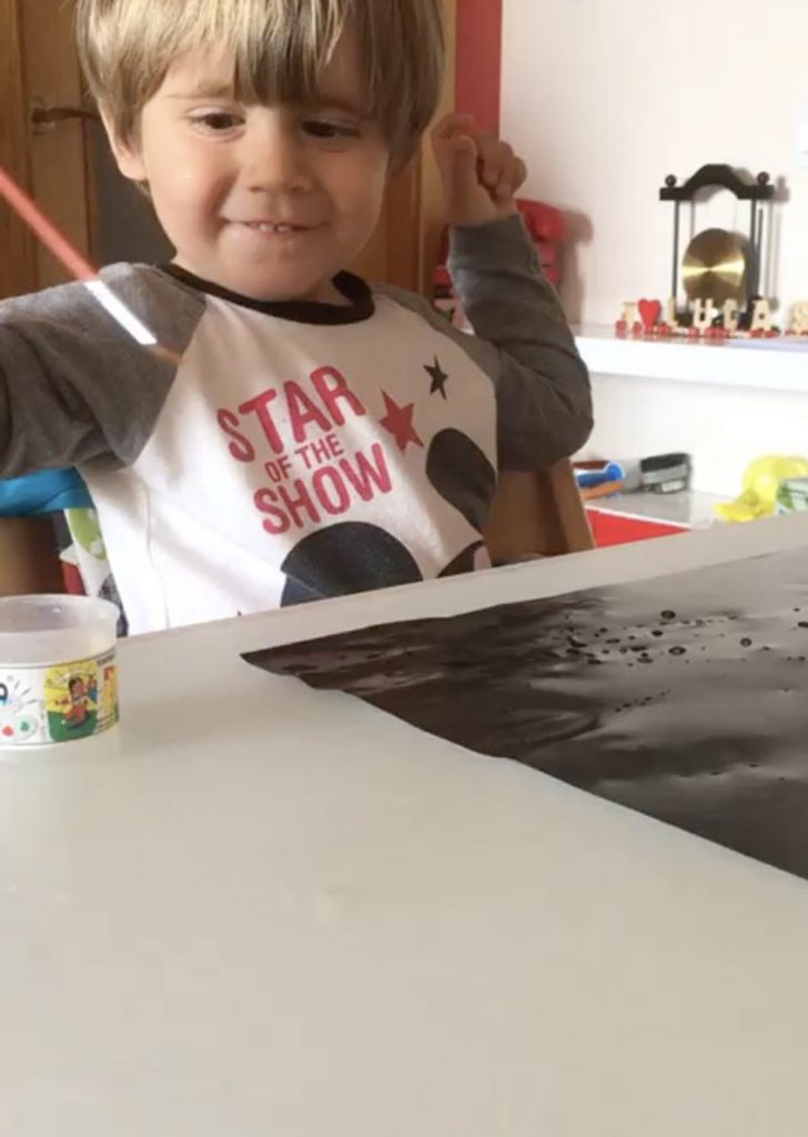 The photo shows my child having fun painting with water over a silky black paper.